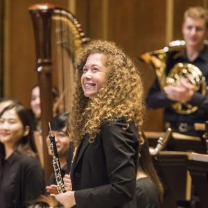 An student oboist smiles with other members of NEC Philharmonia